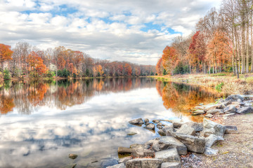 Sunset at Lake Woodglen in Fairfax, Virginia near residential neighborhood, with orange foliage autumn trees forest, water reflection, houses, rocky beach shore