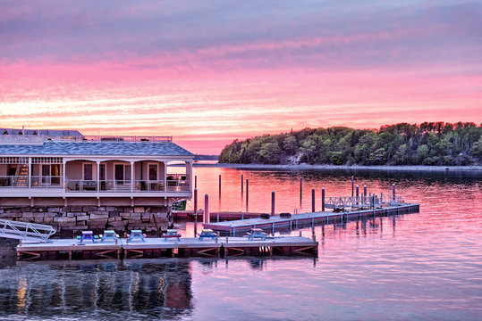 Downtown Bar Harbor village in summer during bright red sunset twilight with waterfront restaurant, pier