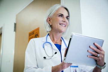 Happy female doctor using digital tablet