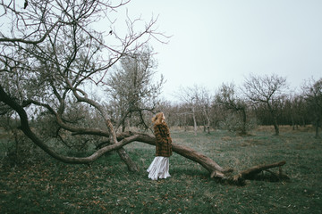 Caucasian woman wearing fur coat near fallen tree