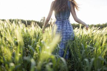 Rear view of woman walking in field of tall grass