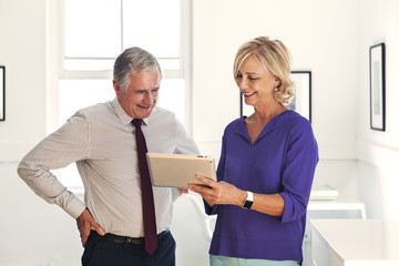 Smiling Caucasian man and woman using digital tablet