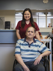 Portrait of smiling nurse and patient in wheelchair