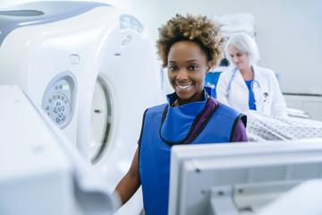 Smiling technician preparing scanner for doctor comforting patient