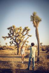 Hispanic man photographing woman in desert