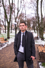 Portrait of a young businessman in a winter park