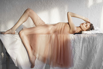 Caucasian woman laying on white sheet