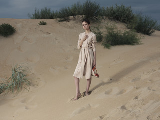 Portrait of woman wearing dress standing on the beach carrying shoes