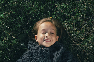 Caucasian girl wearing sweater laying in grass