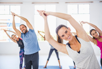 People with arms raised in yoga class