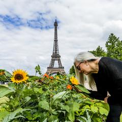 Caucasian woman smelling flowers near Eiffel Tower, Paris, Ile de France, France