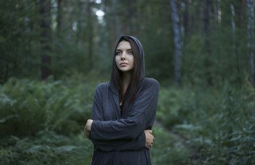 Cold Caucasian woman standing in forest