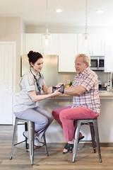 Caucasian nurse wrapping wrist of man