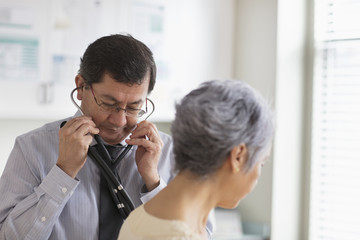 Hispanic doctor with patient using stethoscope