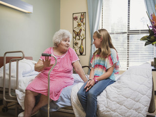 Smiling Caucasian woman sitting on bed talking to granddaughter
