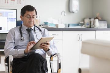 Hispanic doctor reading digital tablet