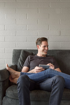 Legs of Caucasian woman on lap of man using digital tablet
