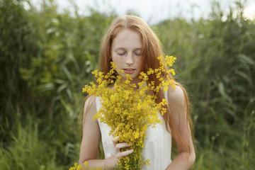 Teenage girl smelling wildflowers