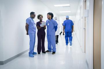 Nurses discussing digital tablet in hospital
