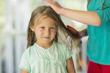 Caucasian girl brushing wet hair of sister