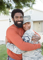Portrait of black woman soldier hugging man