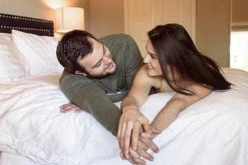 Caucasian couple laying on bed holding hands