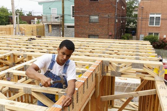 Man hammering nail at construction site