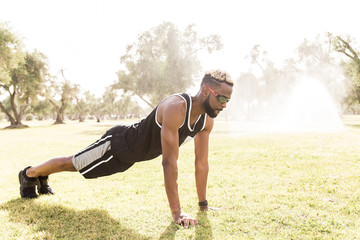 Black man doing push-ups in park