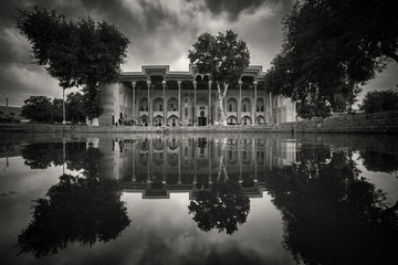 Reflection of trees and ornate building in still pond