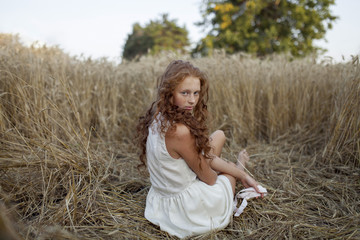 Caucasian girl sitting in wheat