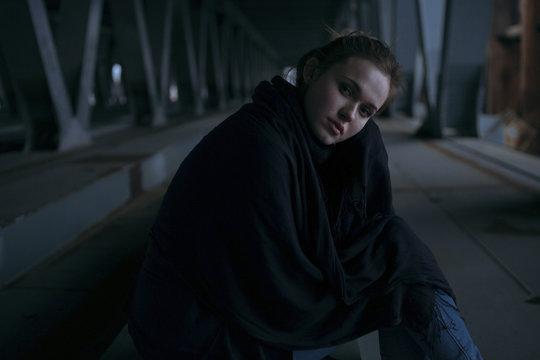 Caucasian woman sitting under bridge
