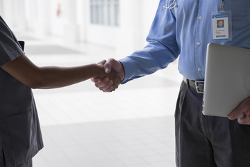 Close up of doctor and nurse shaking hands