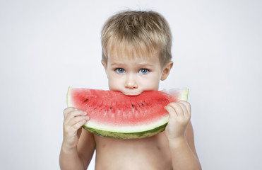 Caucasian boy biting watermelon slice