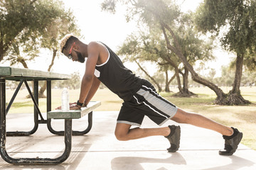 Black man leaning on picnic table in park stretching legs