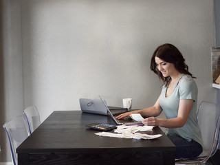 Caucasian woman holding receipt and using laptop