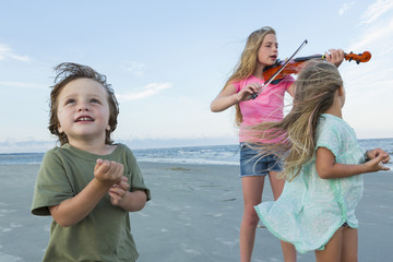 Caucasian girl playing violin on windy beach near brother and sister