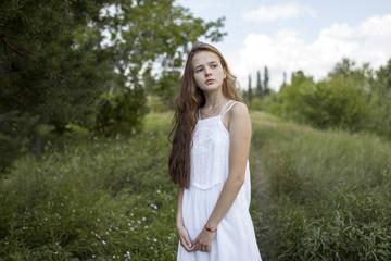 Pensive Caucasian girl standing in field