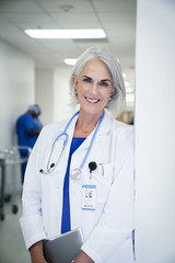 Portrait of smiling female doctor leaning on wall in hospital