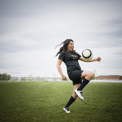 Smiling woman juggling soccer ball on thigh