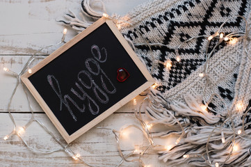 """Word """"hygge"""" written on small framed blackboard, small red heart, woolen knitted blanket and yellow lights for house decoration. Hygge concept. Lifestyle"""