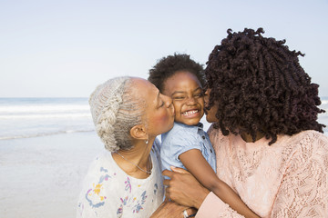 Black mother and grandmother kissing cheeks of girl on beach