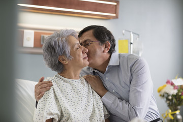 Hispanic man kissing a woman on cheek in hospital bed