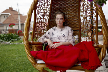 Caucasian girl sitting in hanging chair outdoors