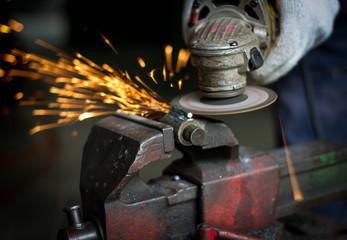 worker using grinder in workshop