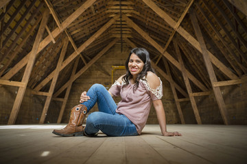 Smiling woman sitting on floor in barn