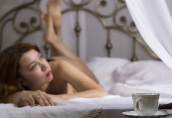 sexy beautiful woman in underwear relaxes on a bed in hotel room. close-up of a tea mug