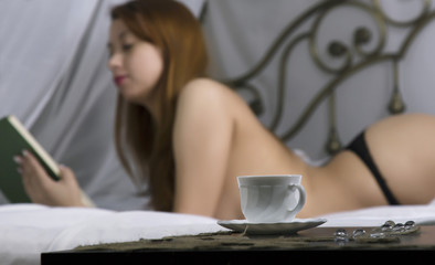 Young beautiful sexy woman reading book on a bed in hotel room