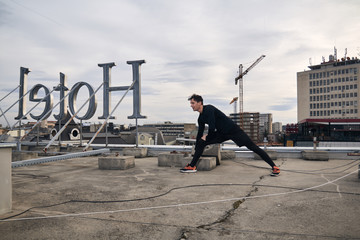 one young man workout stretching outdoors on rooftop. buildings crane behind, urban area city cityscape. Hotel sign backwards.