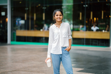 Portrait of young, attractive Indian woman holding a coffee cup in the day and smiling