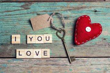 Background with red hearts and vintage key on old boards.
